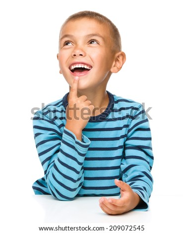 Young boy is daydreaming, isolated over white - stock photo