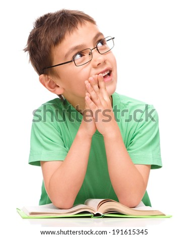 Young boy is daydreaming while reading book and wearing glasses, isolated over white - stock photo