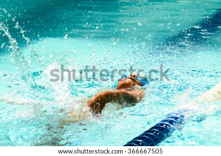 Young boy is doing a competition in a private swimming pool.
