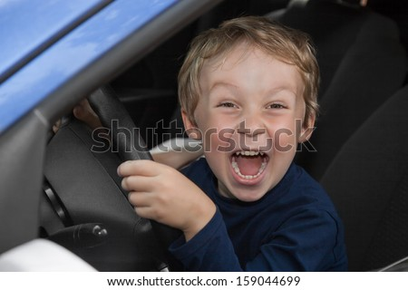 Young boy is happy behind wheel of car - stock photo