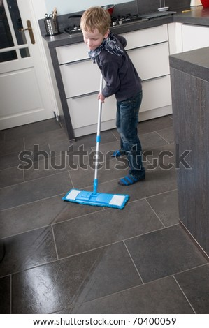 Young boy is learning how to clean a floor - stock photo