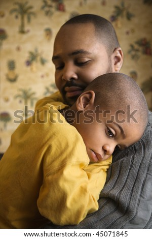 Young boy is lovingly being held by his father.  Vertical shot. - stock photo