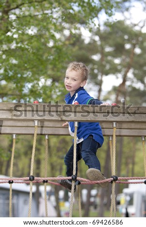 Young boy is playing on a rope. - stock photo