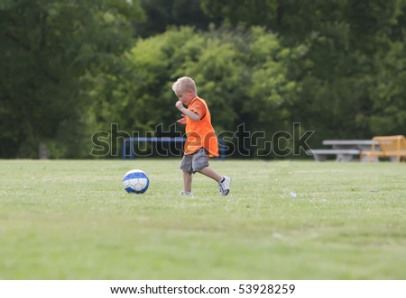 Young boy is playing with a football. - stock photo