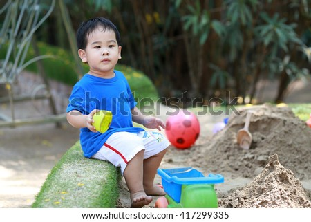 Young boy is playing with sand box on playground - stock photo