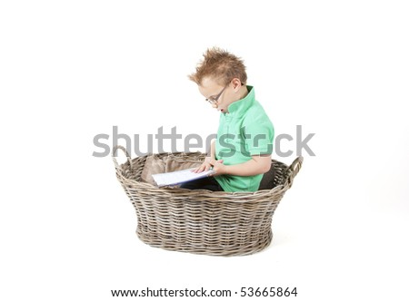 Young boy is reading a book in a basket.