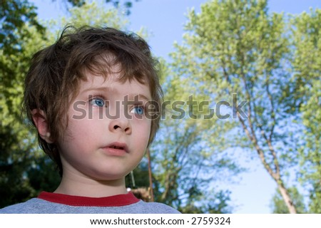 young boy is sad in the summer sun in a park setting - stock photo