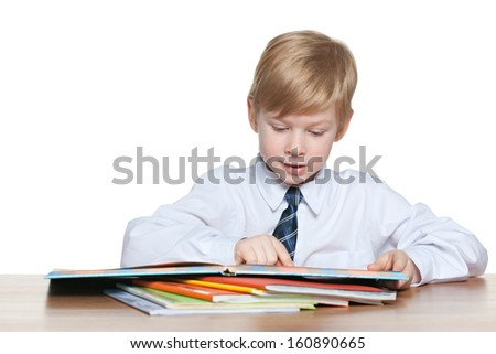 Young boy is sitting at the desk and read a book