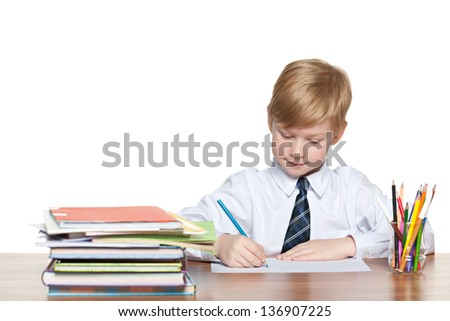 Young boy is sitting at the desk and write