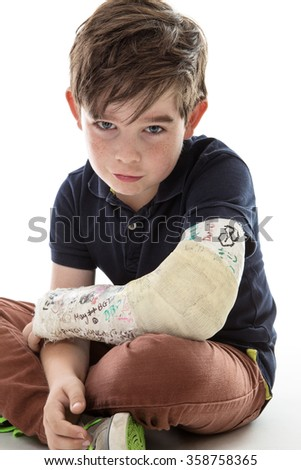Young boy is sitting down and unable to join in because he has broken his arm - stock photo