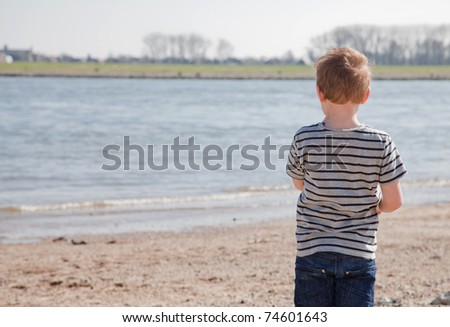 young boy is starring at the river. - stock photo
