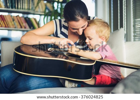 Young boy is trying to play guitar, mother is watching him - stock photo
