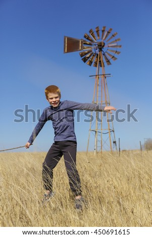 Young boy jumping and playing in the yellow grass, near an old windmill, outdoors on an agricultural farm, on a clear autumn day