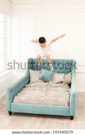 Young Boy Jumping High On Couch At Home Stock Photo