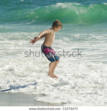 Young boy jumping in ocean waves - stock photo