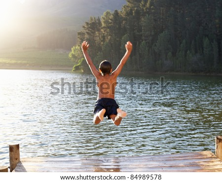 Young boy jumping into lake - stock photo