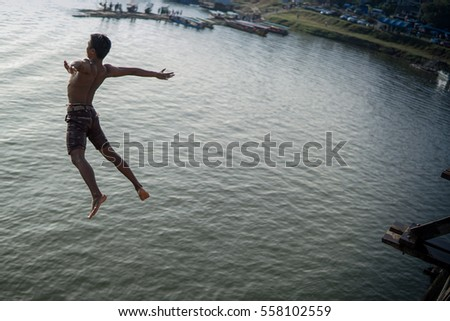 Young boy jumping into river from Mon bridge the longest wooden bridge in Sangkhlaburi, Kanchanaburi, Thailand.