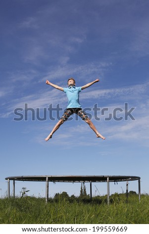 Young boy jumping on a trampoline on green meadow - stock photo