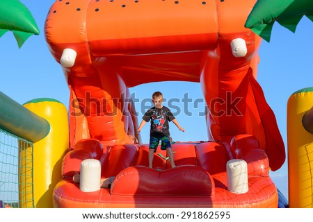 Young Boy Jumping on Bouncy Castle, Having Fun on Inflatable Slide Shaped Like Mouth of Giant Red Hippopotamus - stock photo