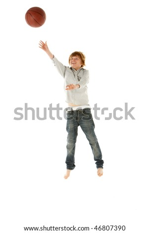 Young Boy Jumping With Basketball In Studio - stock photo
