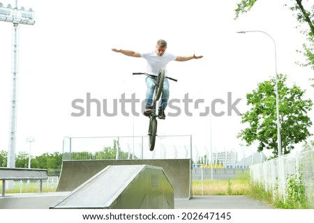 Young boy jumping with his BMX Bike at skate park - stock photo