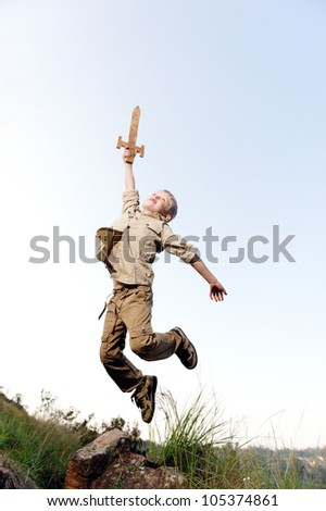Young boy jumping with wooden sword playing an adventure exploring game outside - stock photo
