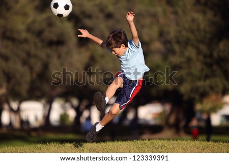 Young boy kicking a soccer ball in the park - authentic action - with copy space - stock photo