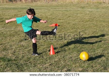 young boy kicking soccer ball - stock photo