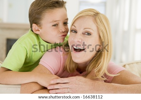 Young boy kissing smiling woman in living room - stock photo