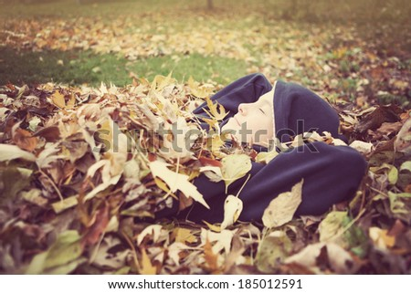 young boy laying in a pile of fall leaves - stock photo