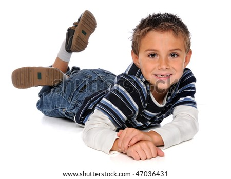 Young boy laying on floor over white background