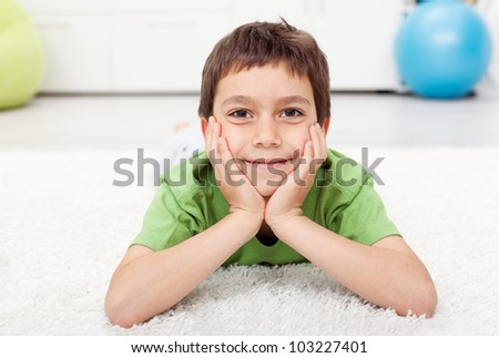 Young boy laying on the floor at home and smiling - stock photo