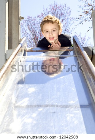 Young boy laying on top of slide at outdoor playground - stock photo