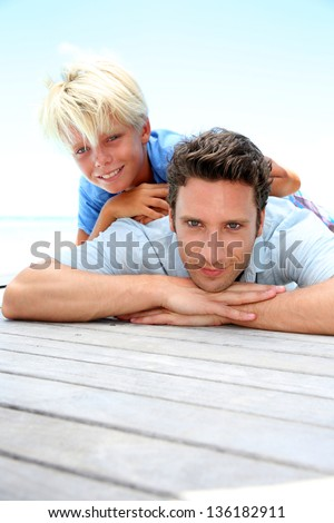 Young boy laying over his dad's back by pool - stock photo