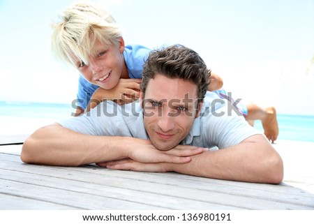 Young boy laying over his dad's back by pool