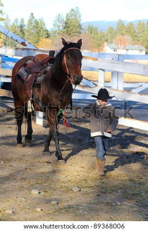 Young boy leading his horse in the riding pen - stock photo