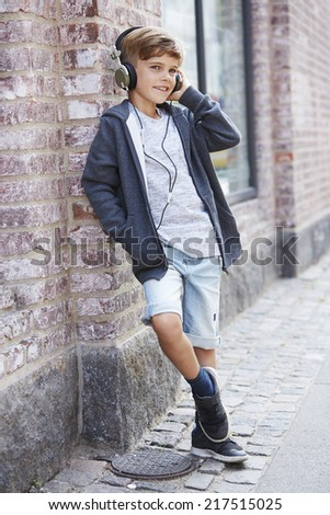 Young boy leaning against wall and wearing headphones   - stock photo