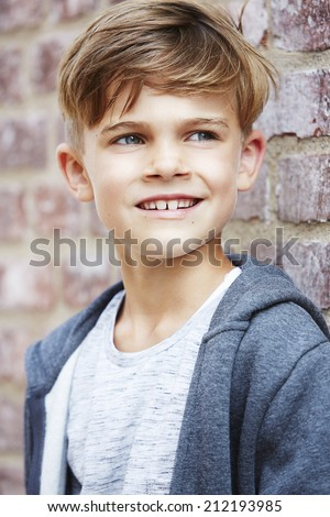 Young boy leaning against wall, looking away  - stock photo
