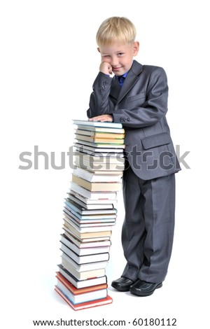 Young Boy leaning over  a Pile of Books - stock photo