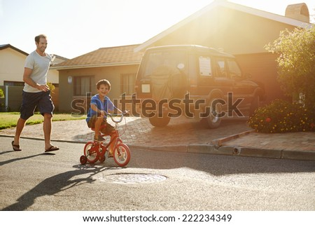 young boy learning to ride bicycle as father teaches him in the suburb street having fun. - stock photo