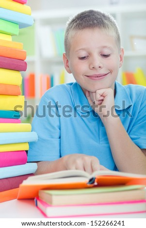 young boy learns from books at home