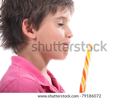 Young boy licking his lips at the sight of his lollypop - stock photo