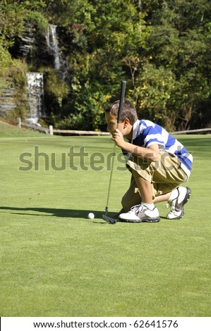 Young boy lining up a shot on a golf course. - stock photo