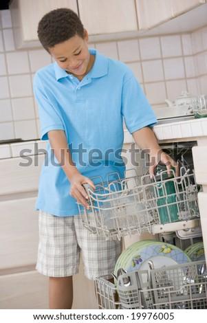 Young Boy Loading Dishwasher - stock photo