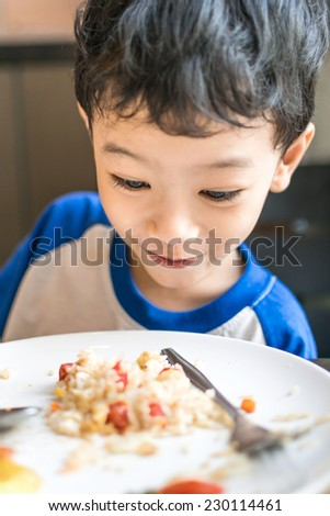 Young boy looking at food excitedly at home, hungry - stock photo
