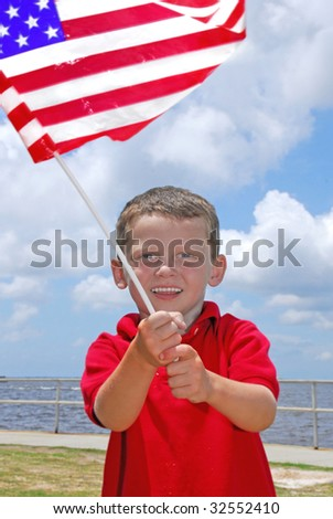 young boy looking happy while waving american flag - stock photo