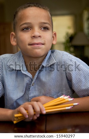 young boy looking off camera while waiting, holding pencils