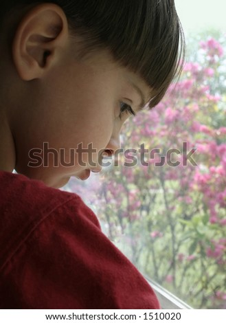 Young Boy Looking Out A Window - stock photo