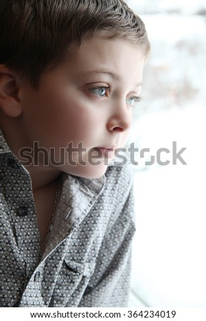 Young boy looking out of the window on a winters day - stock photo