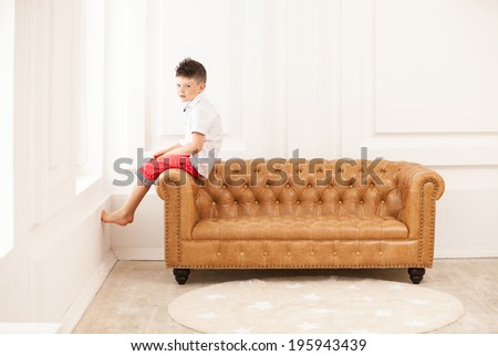 Young boy looking pensively while sitting on couch at home  - stock photo
